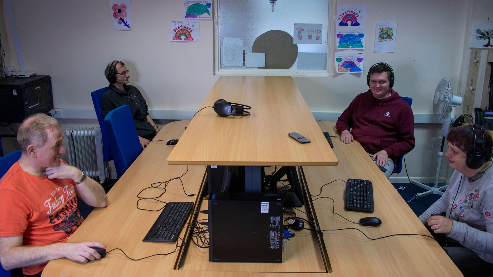 Four service users in the computer room on PCs