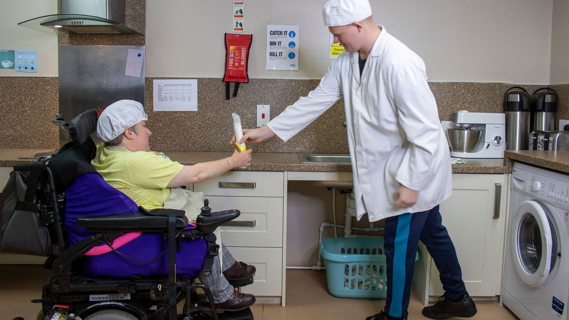 Two services users wearing chef's uniforms helping each other in the Magpies' kitchen