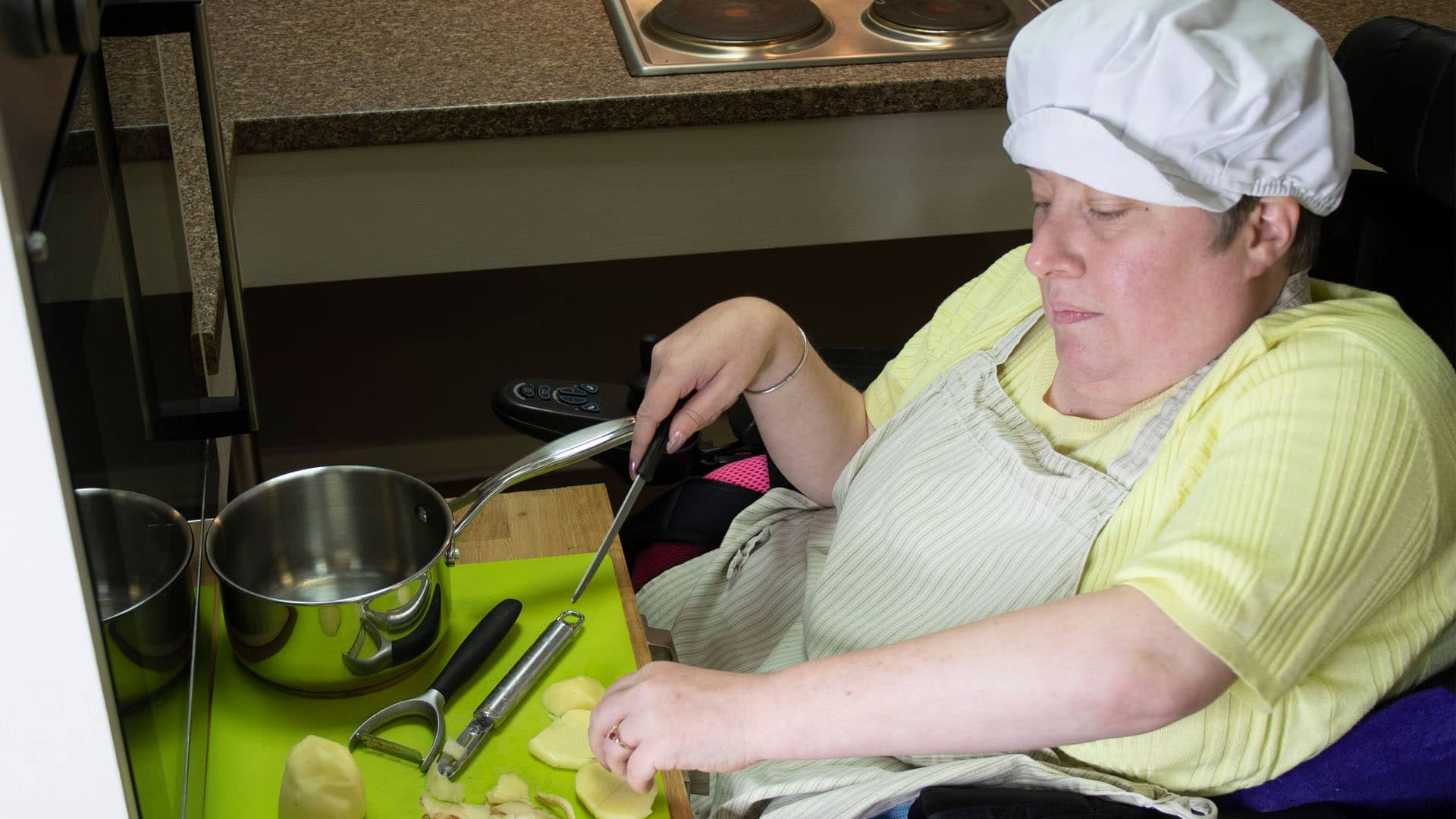 Service user in a mobility chair cooking in the Magpies' kitchen wearing a chef's hat, chopping a potato