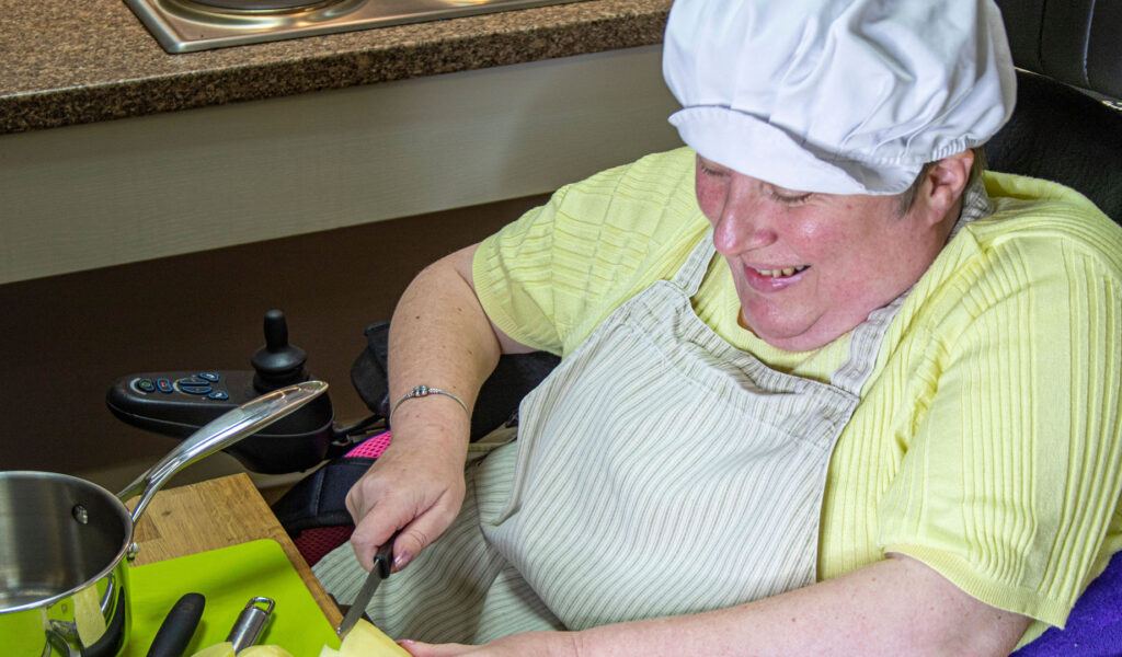 Service user in a mobility chair cooking in the Magpies' kitchen wearing a chef's hat, chopping a potato and smiling