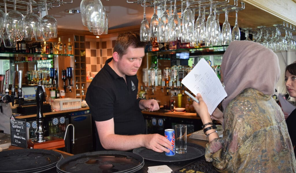 Magpies member behind a bar serving a drink to a customer